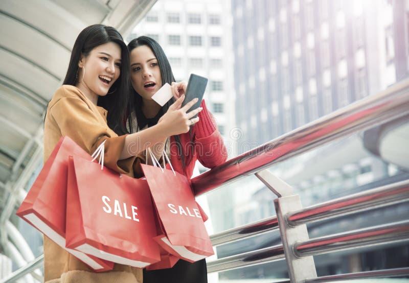 Härliga flickor som rymmer shoppingpåsar genom att använda en smart telefon royaltyfri fotografi