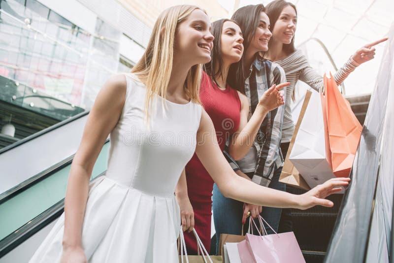 Härliga flickor står på trappa och ser högra Deras uppmärksamhet grips Både asiatisk flicka och flicka i rött arkivbild