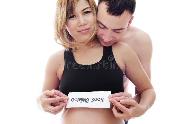 Härliga framtidsföräldrar: hans gravida asiatiska fru och en lycklig makevälkomnande behandla som ett barn att komma snart royaltyfria bilder