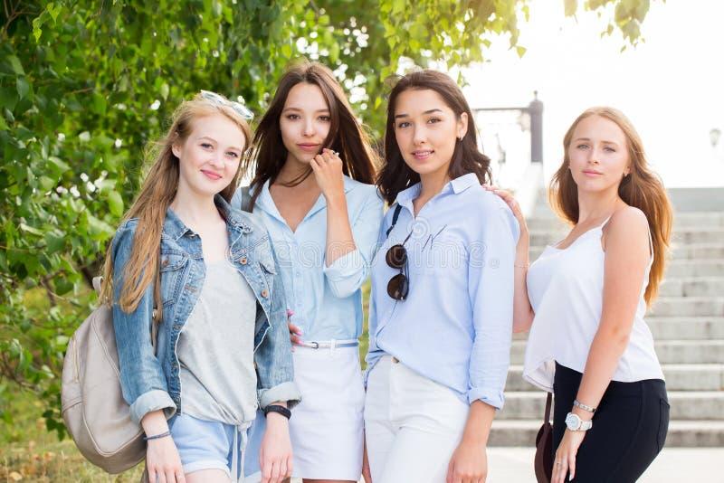 Härliga fyra stilfulla studentflickor som poserar mot naturen och att le royaltyfria bilder