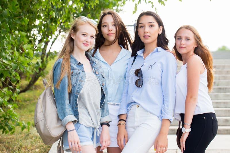Härliga fyra stilfulla studentflickor som poserar mot naturen och att le Sommar går, kamratskap, lycka arkivfoto