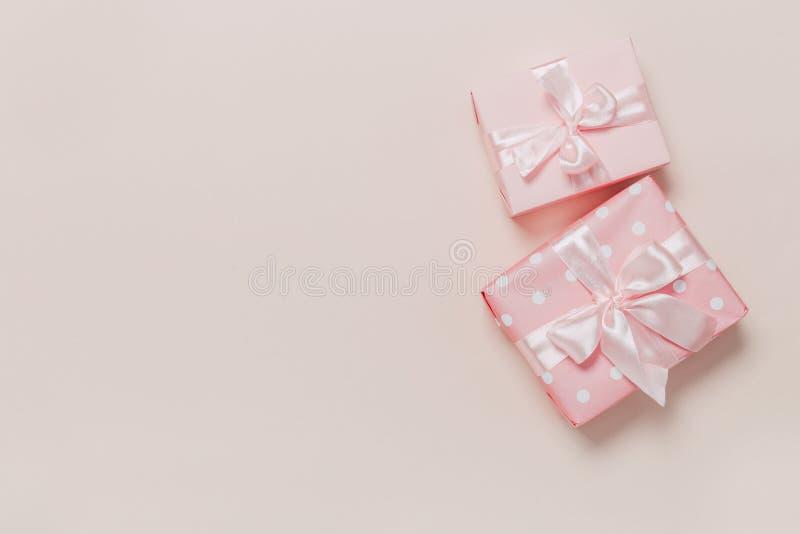 Härliga gåvaaskar som slås in i papper med det guld- och rosa bandet på en beige yttersida Top besk?dar royaltyfri bild