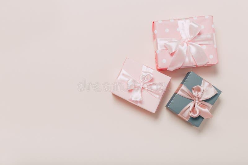 Härliga gåvaaskar som slås in i papper med det guld- och rosa bandet på en beige yttersida Top besk?dar royaltyfri fotografi