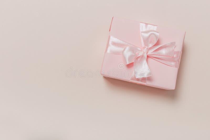 Härliga gåvaaskar som slås in i papper med det guld- och rosa bandet på en beige yttersida Top besk?dar fotografering för bildbyråer