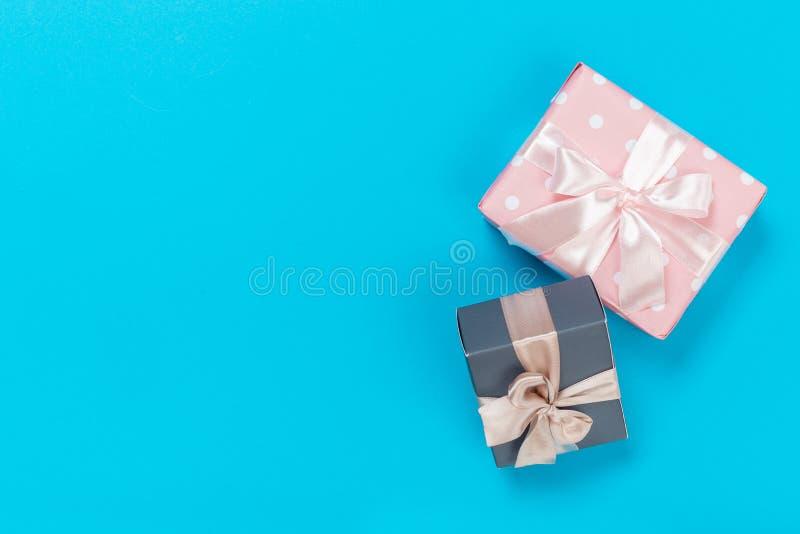 Härliga gåvaaskar som slås in i papper med det guld- och rosa bandet på en blå yttersida Top besk?dar royaltyfria bilder