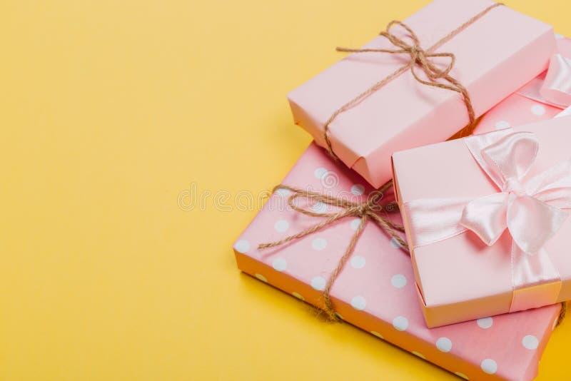 Härliga gåvaaskar som slås in i papper med det röda, guld- och rosa bandet på en gul yttersida B?sta sikt med kopieringsutrymme royaltyfria foton