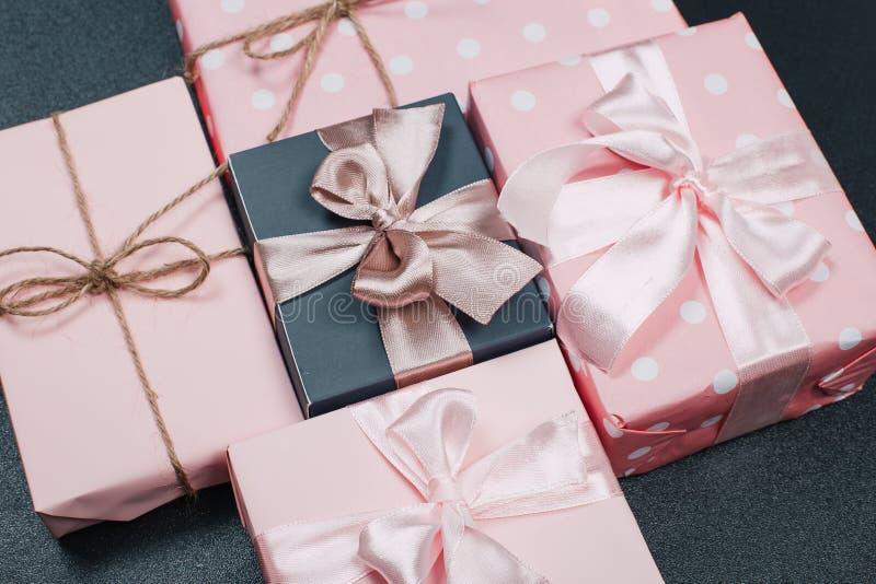 Härliga gåvaaskar som slås in i papper med det röda, guld- och rosa bandet på en svart yttersida B?sta sikt med kopieringsutrymme royaltyfria foton