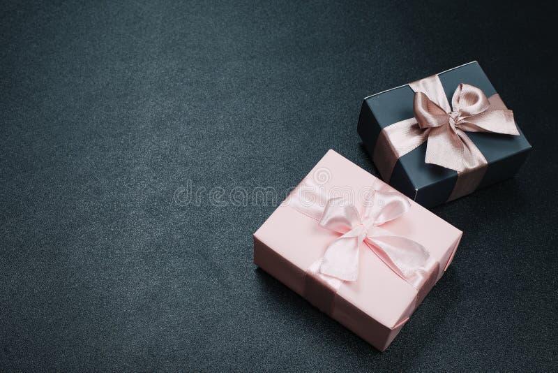 Härliga gåvaaskar som slås in i papper med det röda, guld- och rosa bandet på en svart yttersida B?sta sikt med kopieringsutrymme arkivfoto