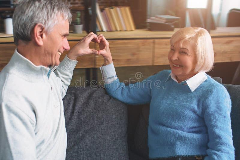 Härliga gamla par sitter tillsammans på soffan och keepien arkivfoton