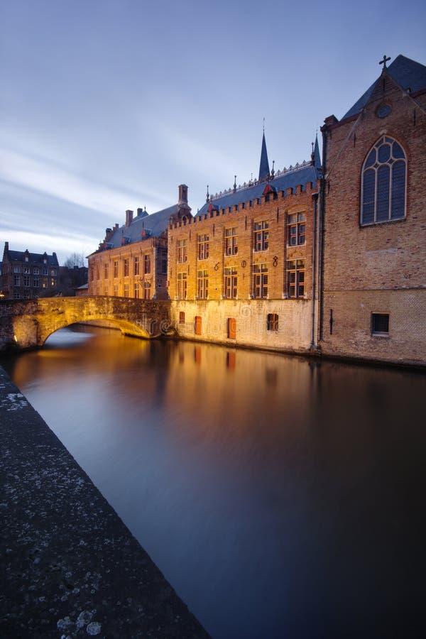 Härliga hus och en överbrygga reflekterad i kanalerna från Bruges (Brugge) - Belgien. arkivbilder