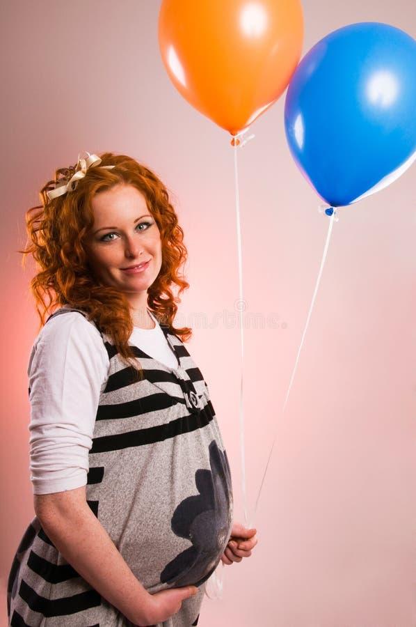 Härliga gravid kvinnaholdingballonger arkivbilder