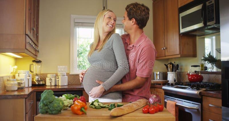 Härliga gravida par, i att krama för kök arkivfoton