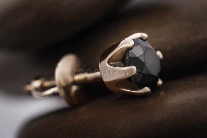 Härliga guld- örhängen med en svart diamant på stenarna arkivfoto