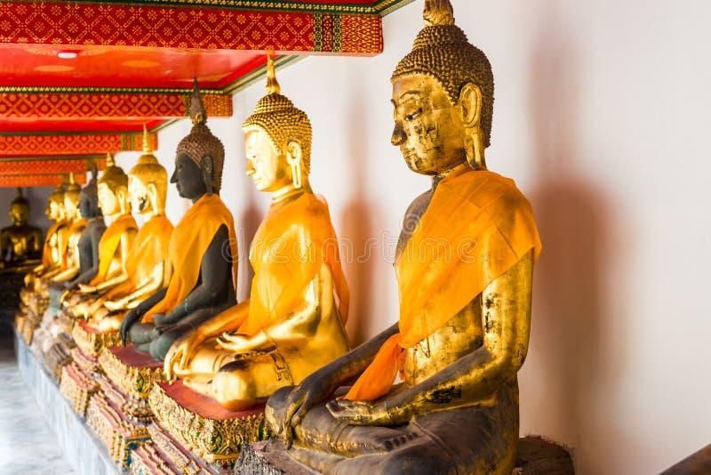 Härliga guld- Buddhastatyer som i rad sitter i tempelnollan arkivfoto
