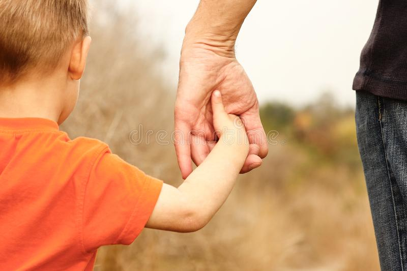 Härliga händer av ett lycklig barn och förälder i naturen parkerar arkivbilder