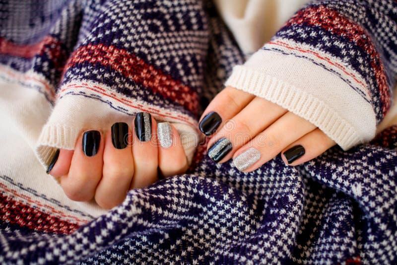 Härliga händer med manikyr i en stucken varm tröja Manikyr - skönhetbehandlingfoto av trevliga manicured kvinnafingernaglar royaltyfri fotografi