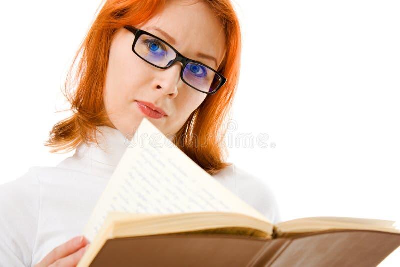 härliga haired bokflickaexponeringsglas läser red arkivfoto