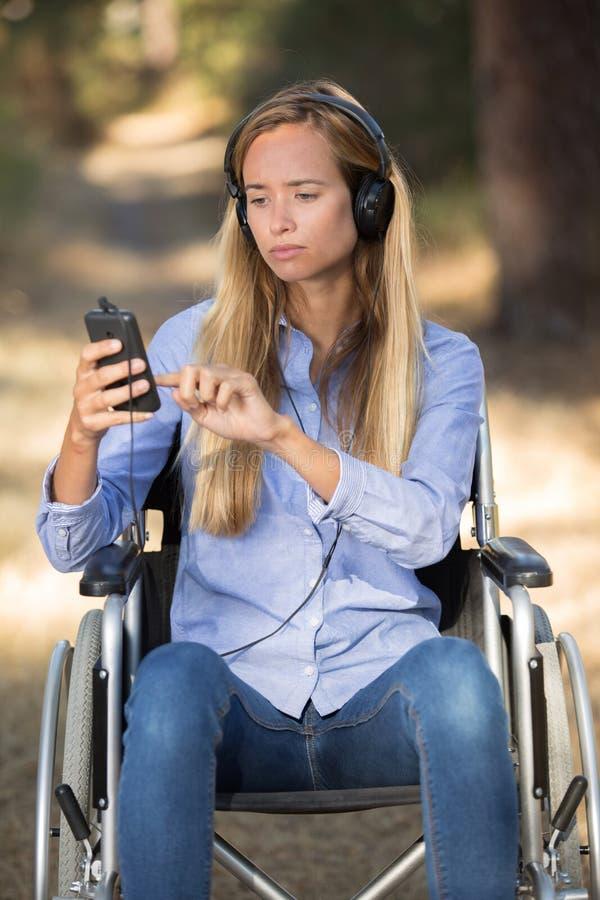 Härliga handikappade unga kvinnor som lyssnar till musik parkerar in royaltyfri foto