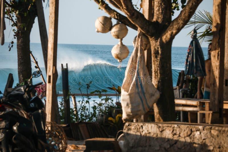 Härliga havvågor som beskådas från ett kafé på stranden på en solig dag med en suddig förgrund arkivfoto