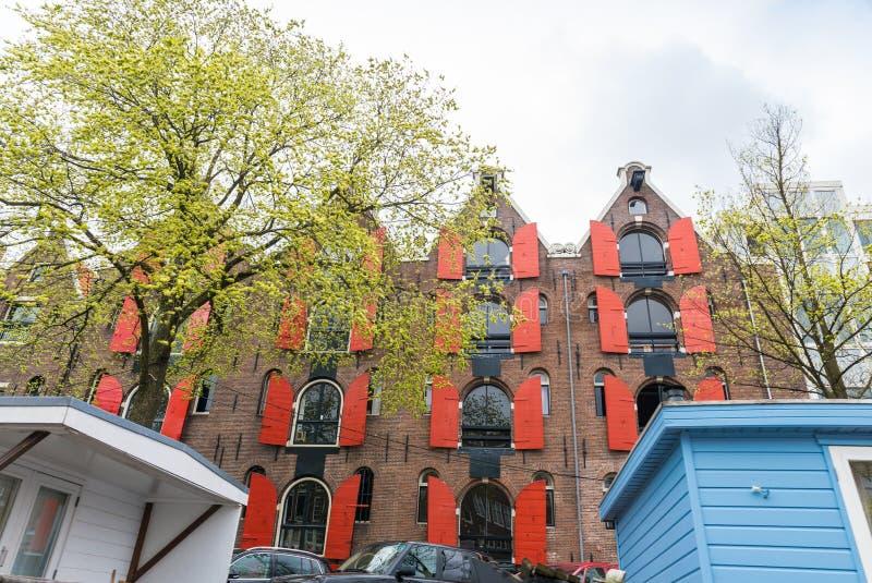 Härliga hus av Amsterdam längs stadskanalen arkivbilder