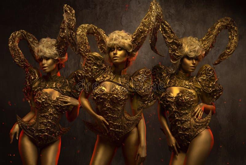 Härliga jäkelkvinnor med guld- dekorativa horn arkivbild