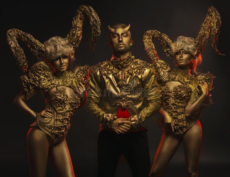 Härliga jäkelkvinnor med guld- dekorativa horn och den stiliga jäkelmannen i dekorativt omslag arkivbilder
