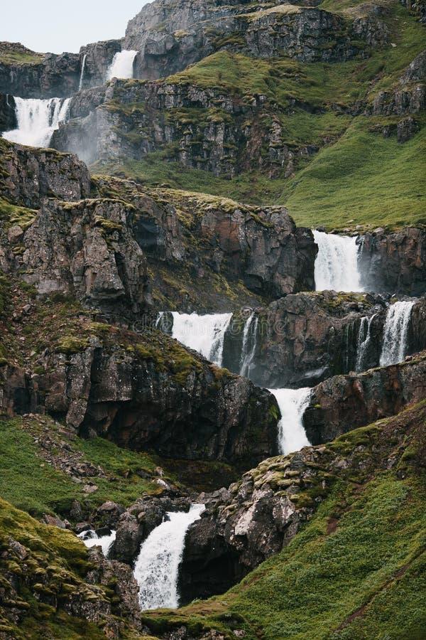härliga kaskader av den sceniska vattenfallet och vaggar royaltyfri fotografi