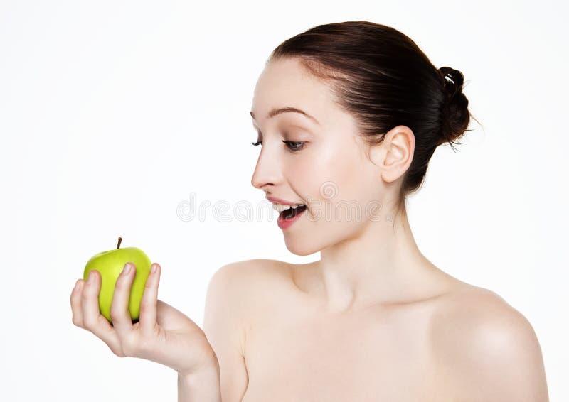 Härliga konditionkvinnor som rymmer det sunda äpplet royaltyfri fotografi