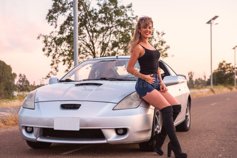 Härliga kortslutningar för ung kvinna som poserar på sportbilen royaltyfria bilder