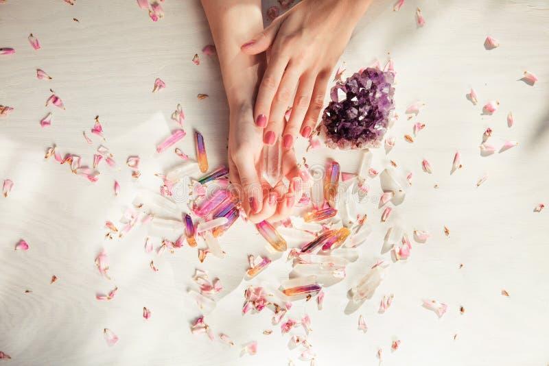 Härliga kvinnahänder med den perfekta violeten spikar polerar på vit träbakgrund som rymmer små kvartskristaller royaltyfri bild