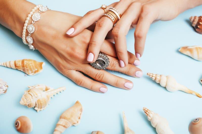 Härliga kvinnahänder med den rosa manikyrinnehavplattan med pärlor och havet beskjuter, det lyxiga smyckenbegreppet arkivfoto