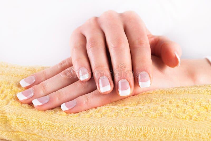 Härliga kvinnahänder med fransman spikar manikyr på den gula handduken arkivfoto