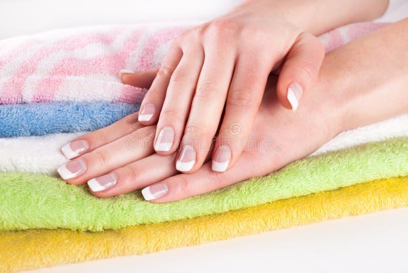Härliga kvinnahänder med fransman spikar manikyr på färgrika handdukar royaltyfri fotografi