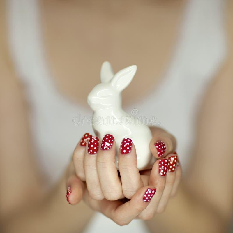 Härliga kvinnahänder med rött spikar polermedelkonst som rymmer den easter kaninen arkivbild