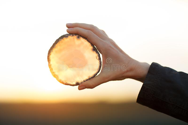 Härliga kvinnahänder som rymmer agat, skivar kristallen i solljuset royaltyfri bild