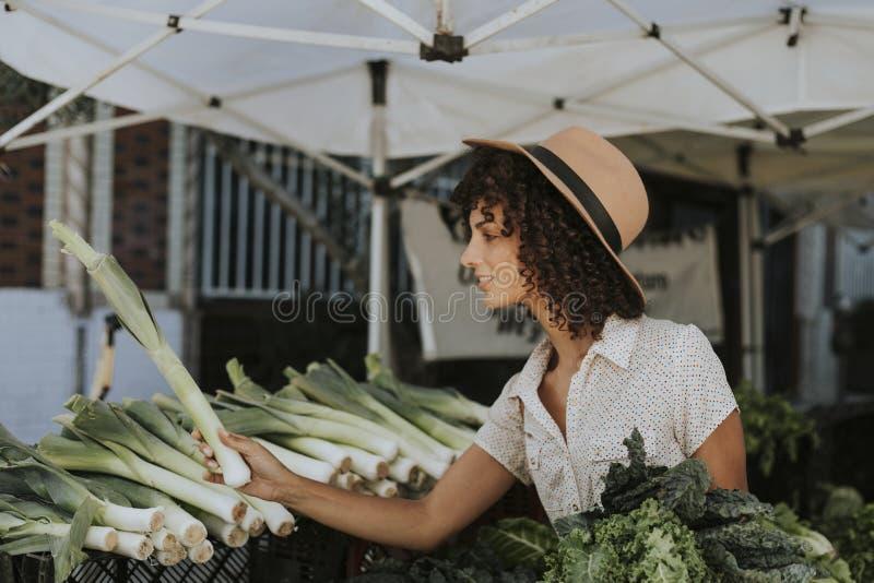 Härliga kvinnaköpandegrönsaker på bönder marknadsför arkivfoton