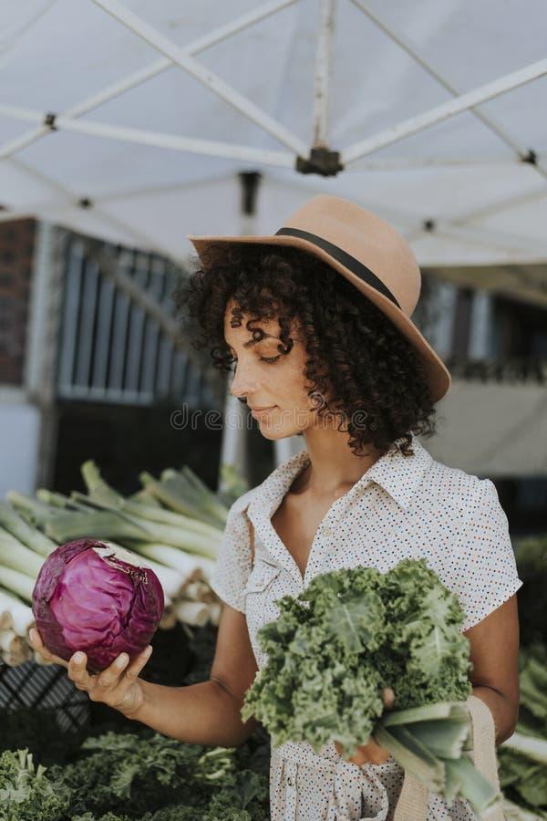 Härliga kvinnaköpandegrönsaker på bönder marknadsför arkivfoto