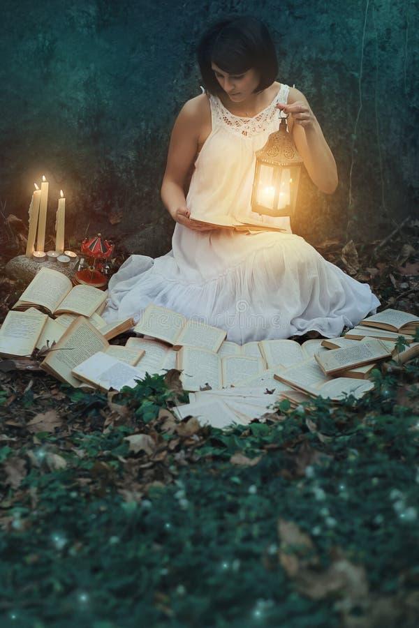 Härliga kvinnaläseböcker i den mörka skogen arkivfoton
