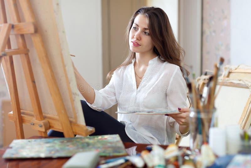 Härliga kvinnamålarfärger på kanfas royaltyfri bild