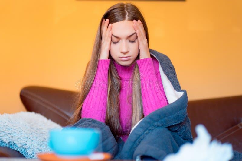 Härliga kvinnas sammanträde i hus och att ha huvudvärk eller oroat, ledset fotografering för bildbyråer