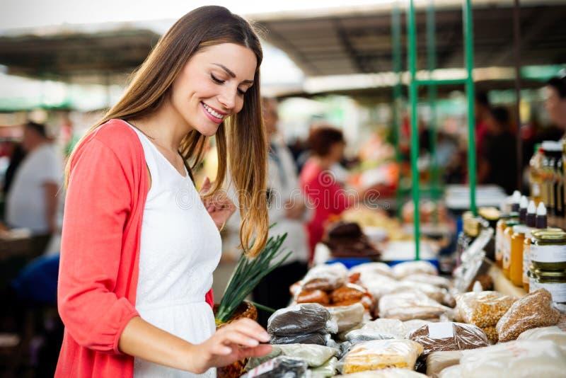Härliga kvinnashoppinggrönsaker och frukter på marknaden royaltyfri bild