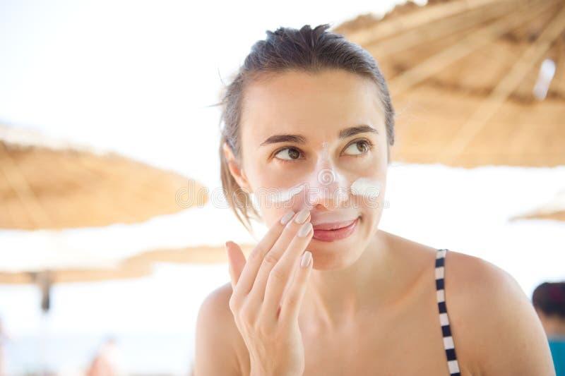 Härliga kvinnasudd vänder mot sunscreen på stranden för skydd royaltyfri fotografi