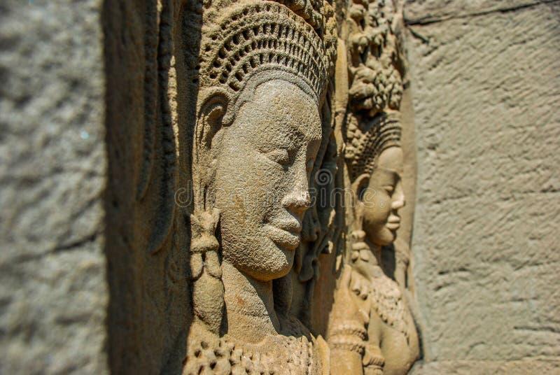 Härliga kvinnliga framsidor som snidas in i väggarna av Angkor Wat royaltyfria bilder