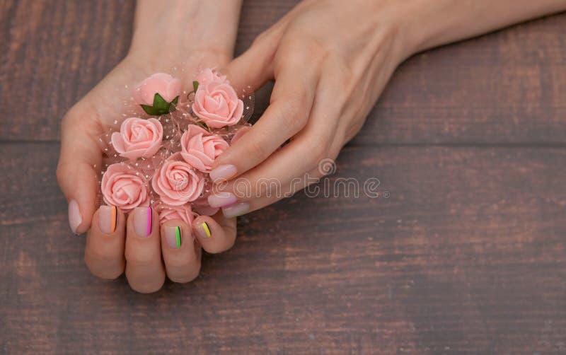 Härliga kvinnliga händer med modern manikyr och rosa blommor på bakgrunden av rött trä arkivbild