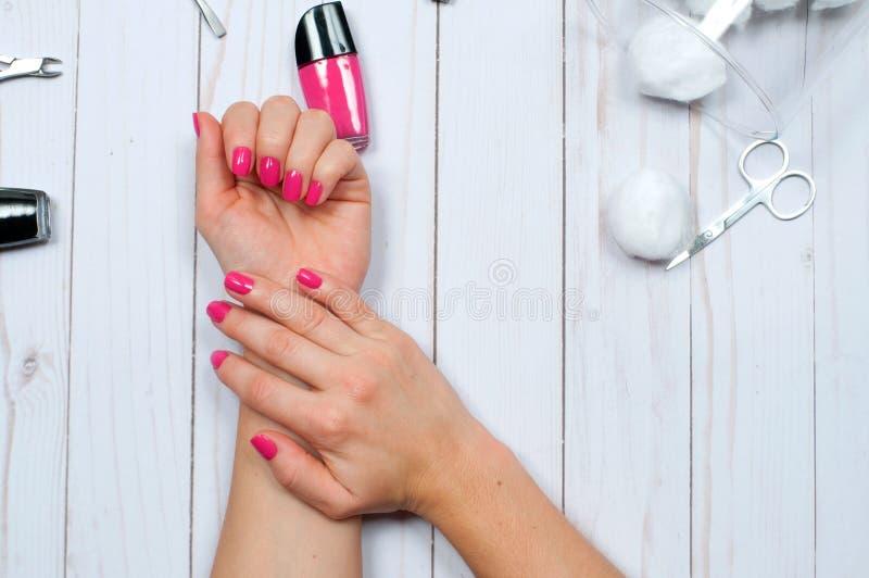 Härliga kvinnliga händer med rosa färger spikar polermedel fotografering för bildbyråer