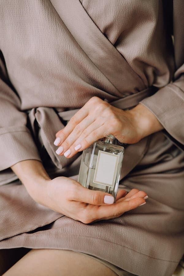 Härliga kvinnliga händer rymmer en glasflaska av doft Delikat morgonförberedelse i en beige siden- dressingkappa arkivbilder