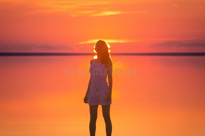 Härliga kvinnliga modellställningar av solen går framme bak horisont på sjösidan För Elton för den salta sjön vatten stillhet und arkivfoton
