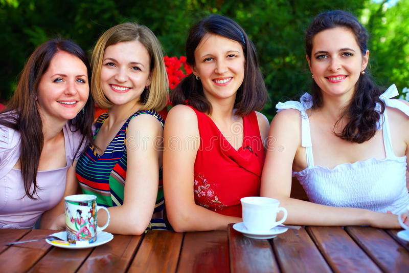 Härliga kvinnliga vänner i sommarkafé royaltyfri bild