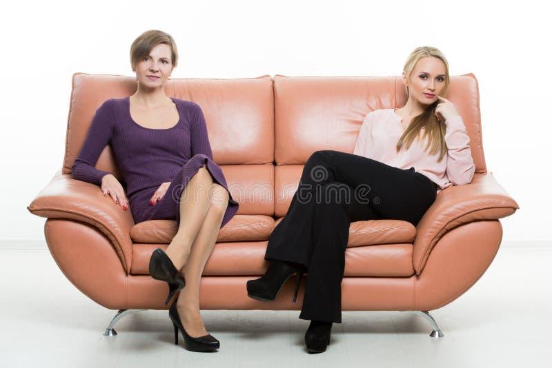 Härliga kvinnliga vänner på soffan Två royaltyfri fotografi