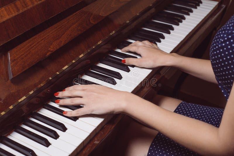 Härliga kvinnlighänder på tangenterna av ett gammalt piano arkivbild